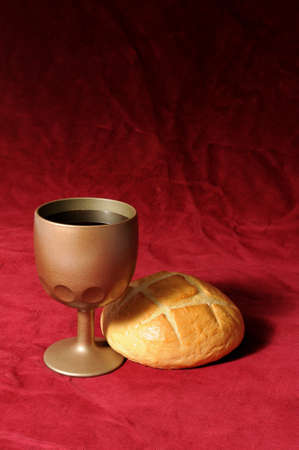 holy eucharist: Communion elements represented by bread and wine over a red background Stock Photo