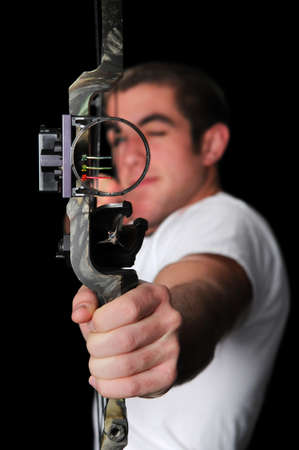 охотник: Young man with bow and arrow aiming straigh isolated over a black background.