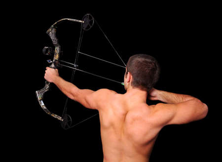 Young archer with bow and arrow aiming high isolated over a black background. photo