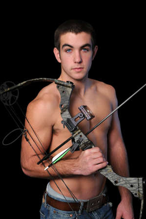 Portrait of young man with bow and arrow isolated over a black background. photo
