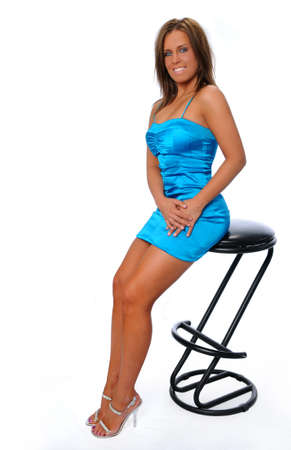 Attractive young woman in blue dress sitting on a stool