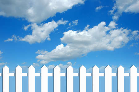 White fence in fromt of blue sky with clouds