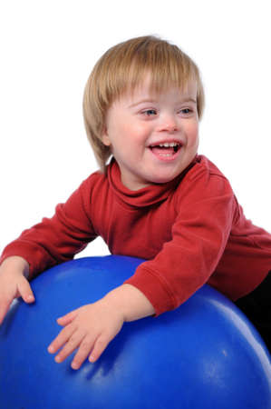 Child with Down Syndrome smiling playing with ball isolated over a white background.