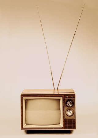 세피아 배경 위에 안테나와 빈티지 TV입니다.