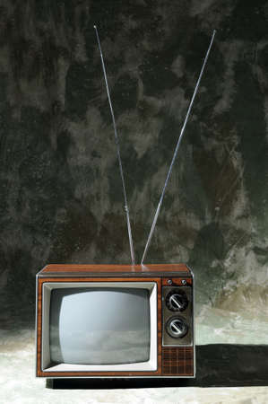 Vintage TV with knobs and antenna over a textured background Stock Photo - 7764525