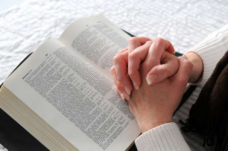 Woman's hands clasped in prayer over an open Bible
