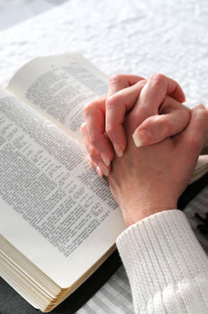 hands clasped: Female hands clasped in prayer ove a Bible
