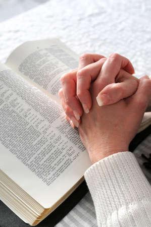 prayer hands: Femmine mani clasped in preghiera ove una Bibbia