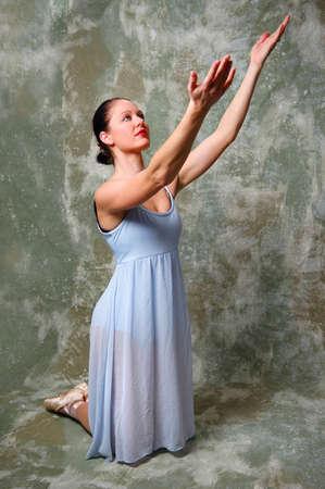 Ballerina kneeling down and raising hands. Banque d'images