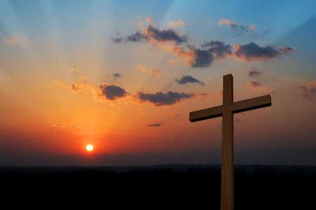 Houten kruis bij zonsondergang met kleurrijke wolken