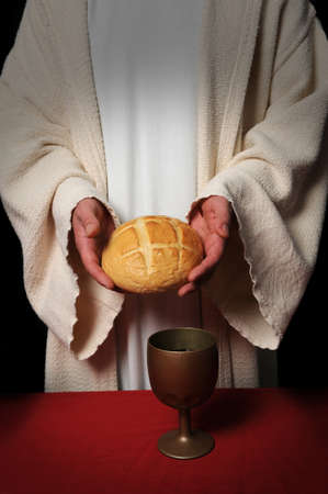 Jesus hands holding the bread at the Communion table photo