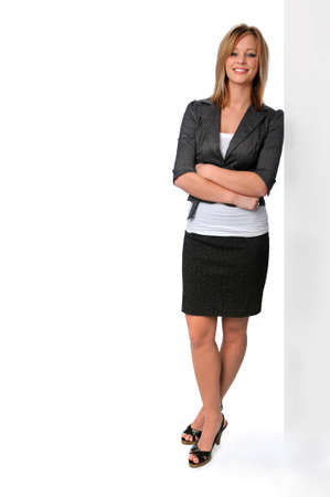 Beautiful and confident young woman in a business suit leaning against wall