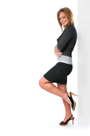 Beautiful young woman in a business suit leaning against wall photo