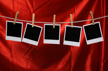 Blank Polaroid photos hanging by a clothespin over a red satin background Stock Photo