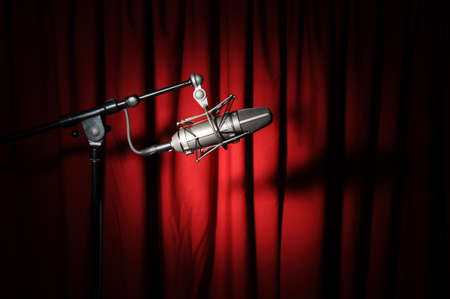 vintage microphone: Vintage microphone with spotlight over a red curtain