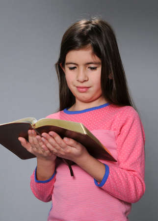 Young girl reading the Bible over a neutral background Stock Photo - 7764542