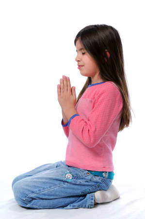 Little girl praying on her knees over a white background 写真素材