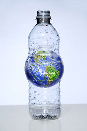 Plastic water bottle with oversized earth inside Stock Photo