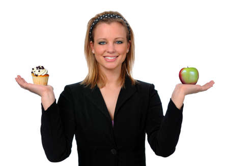 Beautiful young woman holding cupcake and apple photo