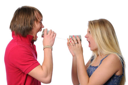 Young couple using tin can phone in an argument photo