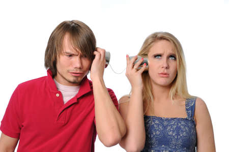 unable: Young couple using a tin can phone and unable to communicate Stock Photo
