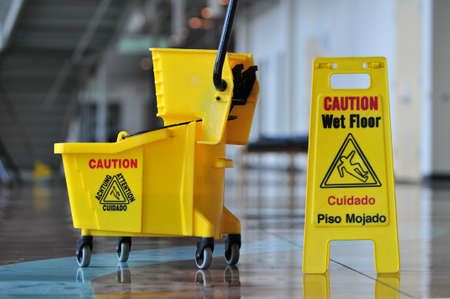 janitorial: Mop bucket and caution sign Stock Photo