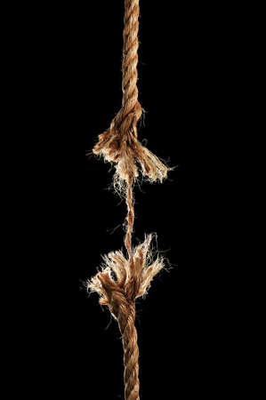 frayed: Taut rope breaking apart isolated over a black background