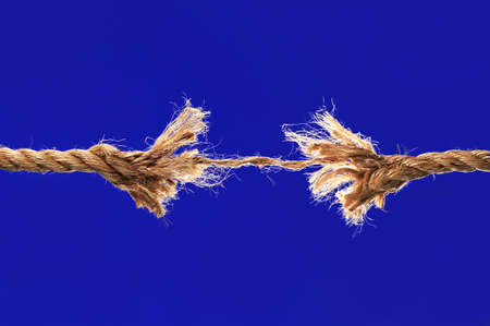 frayed: Rope breaking isolated over a blue background Stock Photo