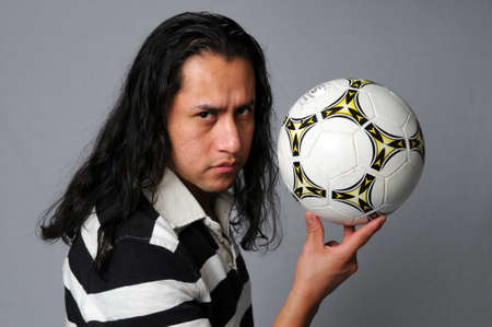 Hispanic man holding soccer ball with his fingers photo