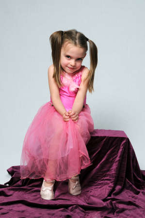 Ballerina girl in pink outfit over a neutrl background photo