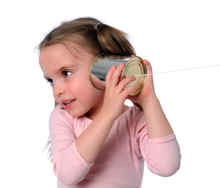 Young girl listening to tin can phone isolated over white Stock Photo - 7793891