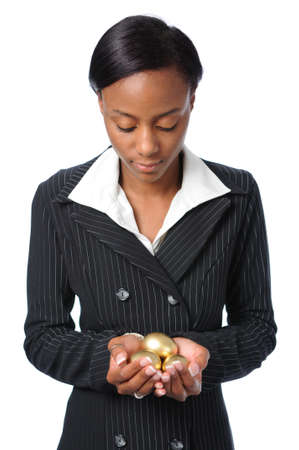 golden eggs: Young African American woman holding gold eggs in her hands