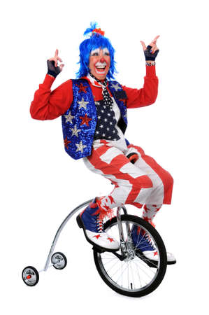 Clown riding a unicycle with training wheels photo