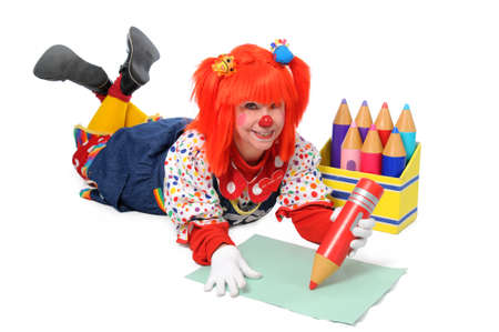 Clown laying down on the floor and writing with large color pencils photo