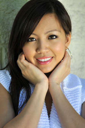 Beautiful Asian woman with hands on face