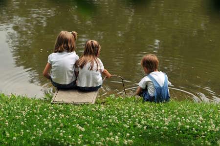 Kinderen spelen met water op de oever van een meer