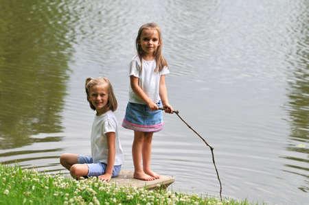 stick children: Young girls playing by a lake