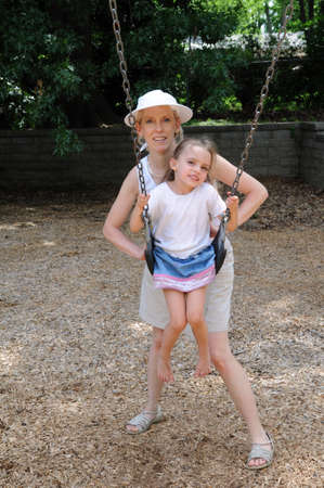 Mother and daughter together on the playground photo