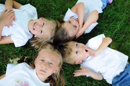 is playful: Niños jugando en la hierba mostrando diferentes expresiones  Foto de archivo