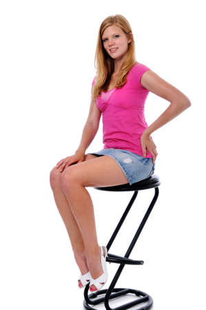 Portrait of beautiful young woman sitting on a stool