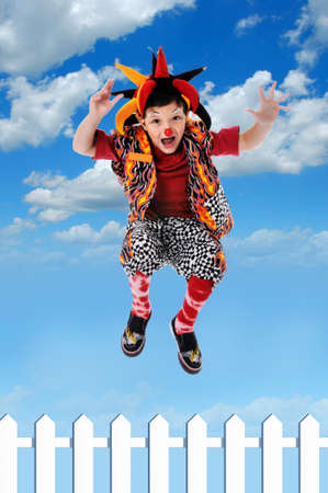 Child clown jumping fence with sky and clouds background photo