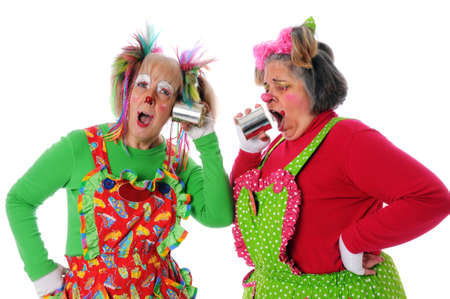 Two clowns using a tin can phone to communicate photo