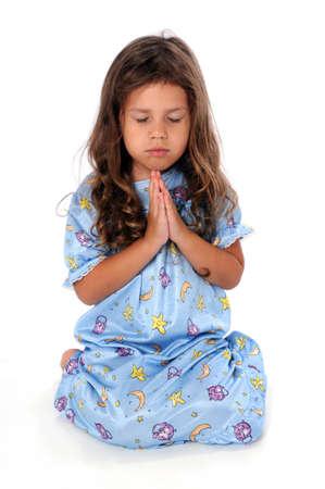 Portrait of little girl dressed in pajamas at bedtime prayer Stock fotó