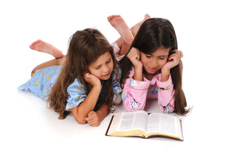 Young girls in pajamas reading the Bible before bedtime Stok Fotoğraf