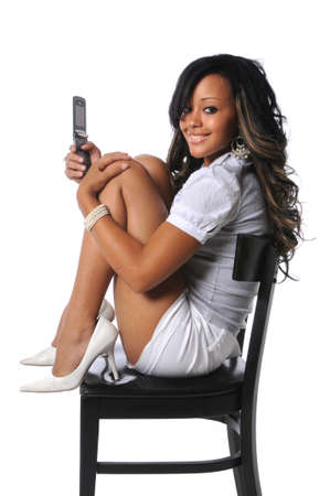 Beautiful African American woman with cell phone sitting on a chair Stock Photo - 7803902