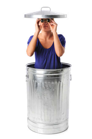 spying: Young woman in trash can spying with binoculars