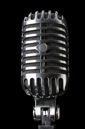 Vintage microphone in close-up view isolated over a black background