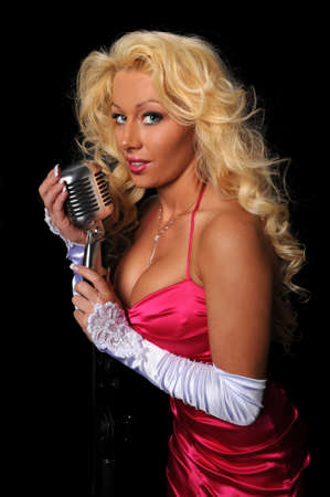Beautiful woman singing into a vintage microphone photo