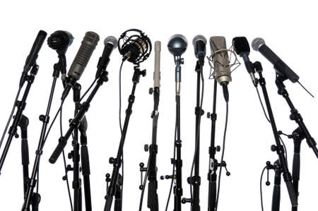 news stand: Microphones aligned together isolated over a white background Stock Photo