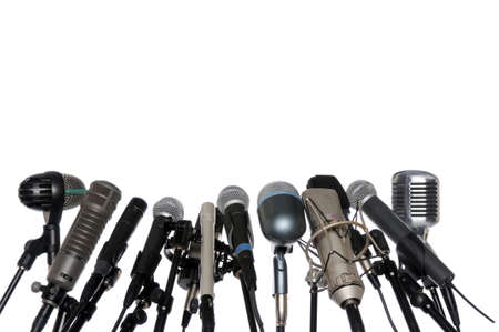 news room: Various microphones aligned at press conference isolated over a white background